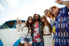 Amis hippies au-dessus de la voiture de monospace montrant le signe de paix Photos stock