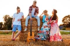 Amis hippies avec la guitare dans un domaine de blé Photos stock