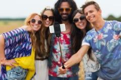 Amis hippies avec le smartphone et le bâton de selfie Image stock