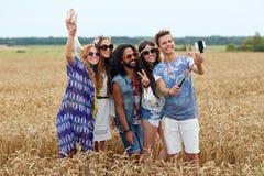 Amis hippies avec le smartphone sur le bâton de selfie Photographie stock