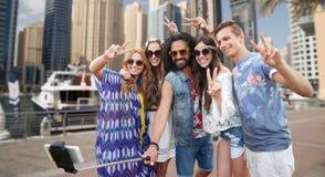 Amis hippies avec le smartphone sur le bâton de selfie Photo stock