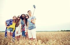 Amis hippies avec le smartphone sur le bâton de selfie Image libre de droits