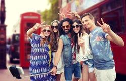 Amis hippies avec le smartphone sur le bâton de selfie Photos libres de droits