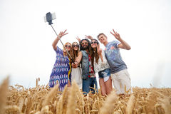 Amis hippies avec le smartphone sur le bâton de selfie Photo libre de droits