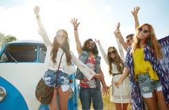 Amis hippies de sourire ayant l'amusement au-dessus de la voiture de monospace Photographie stock libre de droits