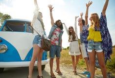 Amis hippies de sourire ayant l'amusement au-dessus de la voiture de monospace Photo libre de droits