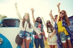Amis hippies de sourire ayant l'amusement au-dessus de la voiture de monospace Images stock