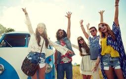 Amis hippies de sourire ayant l'amusement au-dessus de la voiture de monospace Photos stock