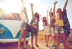 Amis hippies de sourire ayant l'amusement au-dessus de la voiture de monospace Photos libres de droits