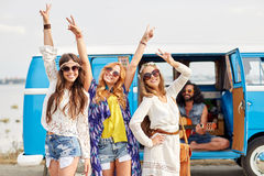Amis hippies heureux ayant l'amusement au-dessus de la voiture de monospace Image libre de droits