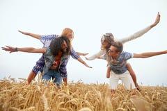 Amis hippies heureux ayant l'amusement sur le gisement de céréale Photos stock