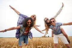 Amis hippies heureux ayant l'amusement sur le gisement de céréale Photographie stock libre de droits