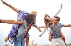 Amis hippies heureux ayant l'amusement sur le gisement de céréale Image libre de droits