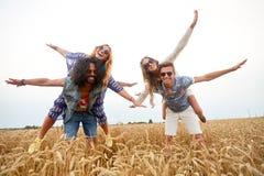 Amis hippies heureux ayant l'amusement sur le gisement de céréale Image stock