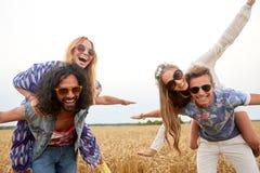 Amis hippies heureux ayant l'amusement sur le gisement de céréale Photographie stock