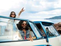 Amis hippies heureux dans la voiture de monospace sur l'île Photo stock