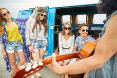 Amis hippies heureux jouant la musique au-dessus du monospace Photo stock