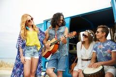 Amis hippies heureux jouant la musique au-dessus du monospace Photographie stock