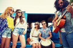 Amis hippies heureux jouant la musique au-dessus du monospace Images libres de droits