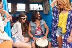 Amis hippies heureux jouant la musique dans le monospace Photographie stock libre de droits