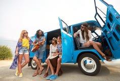 Amis hippies heureux jouant la musique dans le monospace Photos stock