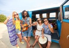 Amis hippies heureux jouant la musique dans le monospace Photos libres de droits