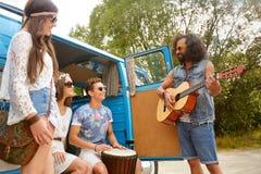 Amis hippies heureux jouant la musique dans le monospace Images libres de droits