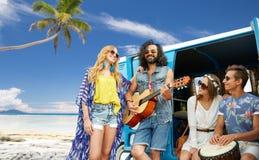 Amis hippies jouant la musique au-dessus du monospace sur la plage Photo libre de droits