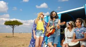 Amis hippies jouant la musique au monospace en Afrique Photos stock
