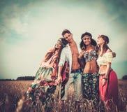Amis hippies multi-ethniques dans un domaine de blé Images stock