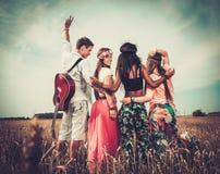 Amis hippies multi-ethniques dans un domaine de blé Images libres de droits