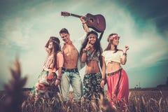 Amis hippies multinationaux avec la guitare dans un domaine de blé Images libres de droits