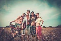 Amis hippies multinationaux dans un domaine de blé Photographie stock libre de droits