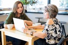 Amis hispaniques de femmes à l'aide de l'ordinateur portable au café Image stock