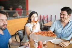 Amis hispaniques gais ayant l'amusement mangeant de la pizza dans la pizzeria Images stock