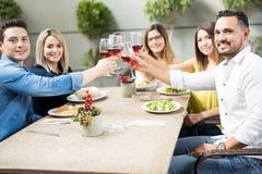 Amis hispaniques grillant avec du vin Images stock