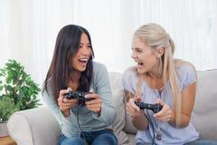 Amis idiots jouant des jeux vidéo et rire Photographie stock