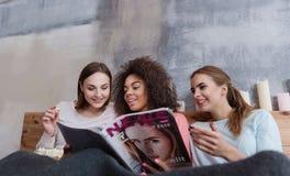 Amis impliqués lisant et discutant la magazine à la maison Image libre de droits