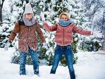 Amis insouciants jouant avec la neige dans la forêt Photos stock