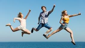 Amis insouciants sautant par l'eau d'océan de mer Image stock