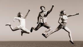 Amis insouciants sautant par l'eau d'océan de mer Images libres de droits