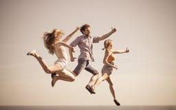 Amis insouciants sautant par l'océan de mer Photo libre de droits