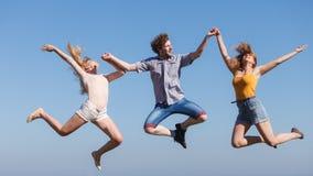 Amis insouciants sautant sur le fond de ciel Photographie stock libre de droits
