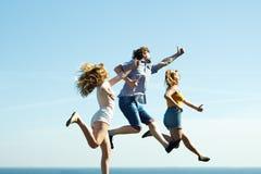 Amis insouciants sautant sur le fond de ciel Photos stock