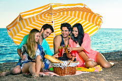 Amis insouciants sous le parapluie jaune avec des boissons Photos stock