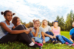 Amis internationaux de sourire s'asseyant sur l'herbe Photo stock