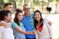 Amis internationaux prenant le selfie en parc Images stock