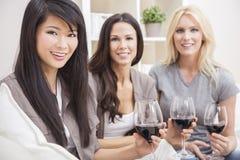 Amis interraciaux de femmes de groupe buvant du vin Photo stock