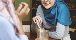 Amis islamiques de femmes appréciant et parlant dans le café Photo stock