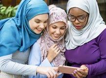 Amis islamiques de femmes regardant le téléphone intelligent avec le sourire Photo libre de droits